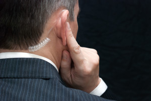 25307685 - close-up of a secret service agent listening to his earpiece, over the shoulder.